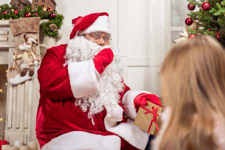 Please, keep my secret. Surprised fat bearded man in red and white costume is putting gifts under fir-tree secretly. Curious girl is looking at Santa Stock Photo