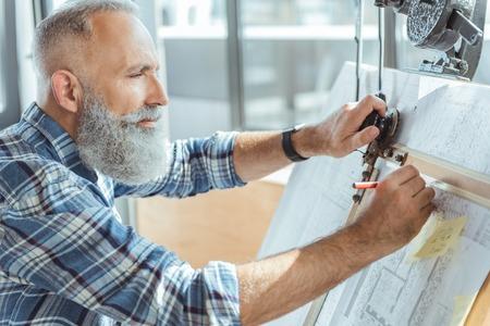 Aangename serieuze oude man werkt aan een professioneel bord Stockfoto