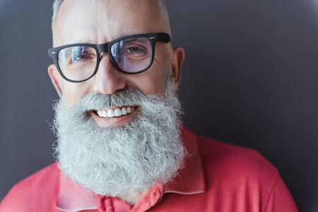 유쾌한 세련된 회색 머리 남자가 기쁨을 표현합니다.
