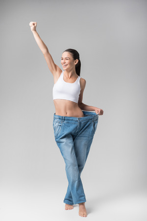 Glad thin young woman is satisfied with her figure