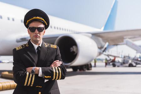 Serious aviator locating near plane Фото со стока