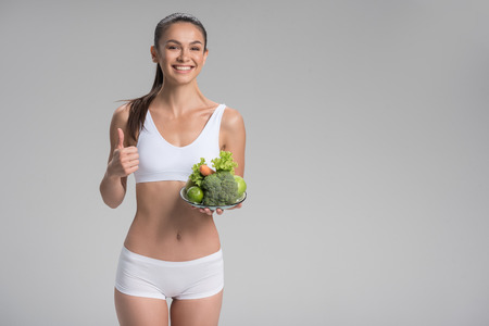 Happy young slim woman keeping on the diet with enjoyment