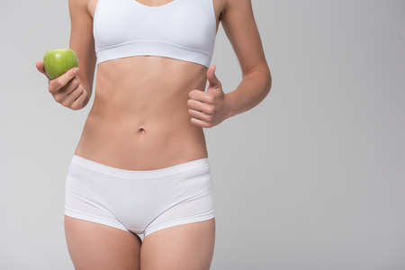 Thin young woman prefers to eat fruits Stock Photo