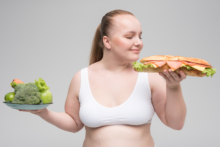 Hungry thick woman enjoying smell of unhealthy burger