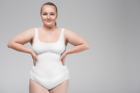Cheerful chubby young woman is satisfied with her figure Фото со стока