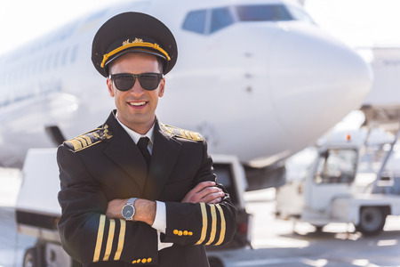 Hilarious smiling aviator locating near plane