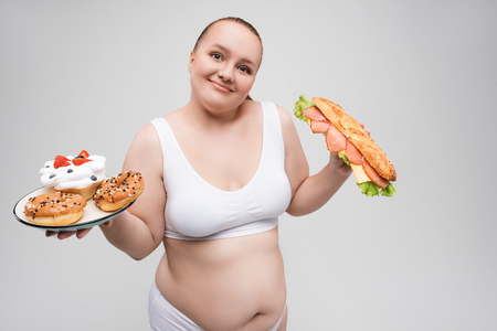 Happy thick young woman holding burger and sweets Zdjęcie Seryjne - 87547762