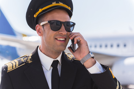 Joyous smiling pilot speaking on phone