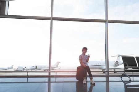 Fröhliches lächelndes männliches Kind im Flughafen Standard-Bild - 87547770