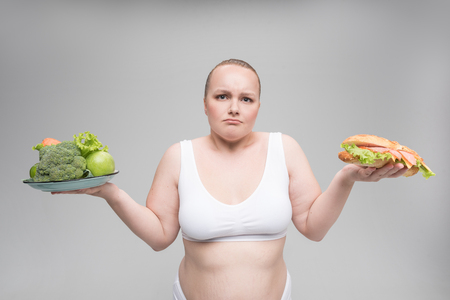 Confused fat woman making choice of nutrition