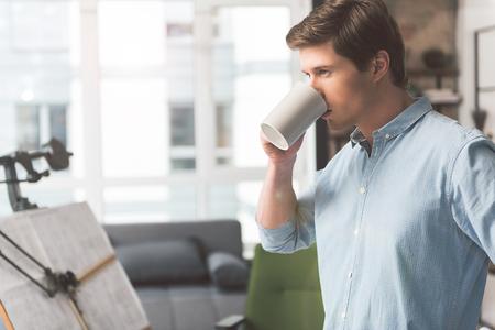 Pleasant engineer is enjoying fresh espresso thoughtfully