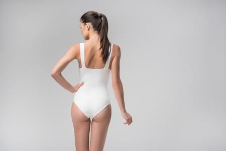 Sensual slim girl standing with arm akimbo
