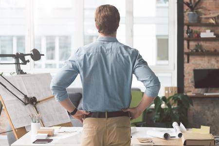 エレガントな若い男の背面図は、両手を腰に当て事務所で休んでいます。彼は職場の前に立って、窓から見て 写真素材