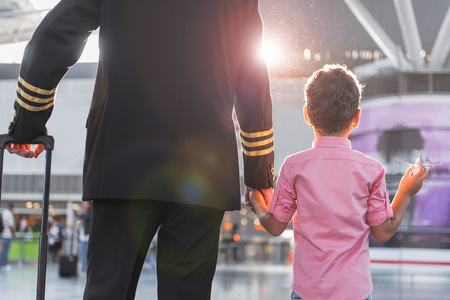 Pilot is holding hand his little son. They locating in airport. Focus on back. Low angle Stock Photo