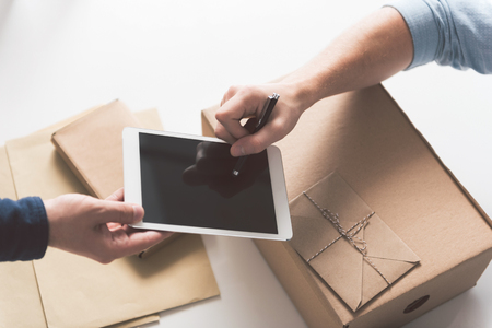 Modern technology. Close-up top view of stylus in hand of man and digital screen in hand of courier. Male is putting his signature after accepting delivery. Boxes and envelopes in background 免版税图像