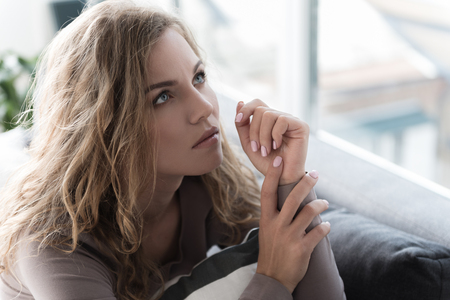 Thoughtful woman situating in apartment Stock fotó