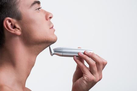 魅力的なかわいい男が毛にワイヤレス デバイスを使用してください。
