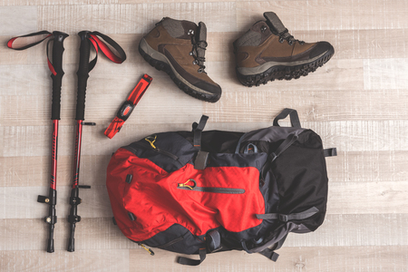 Red rucksack is near sticks for Nordic walking and convenient shoes on floor in room. Top view close up. Nobody Stok Fotoğraf - 87692708