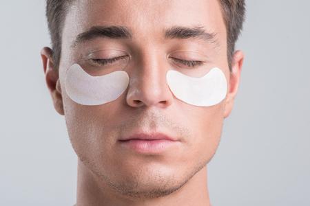 真面目な男は皮膚の治療を楽しんでいます。 写真素材