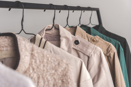 Various coats are hanging on metal modern hangers. Focus on certain article of clothing. Copy space on right side and close up. Nobody