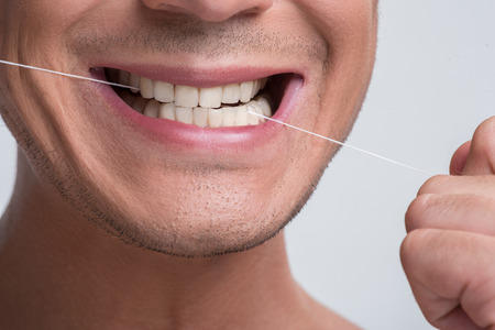 Dental health concept. Close-up of mouth of cheerful young pleasant guy who is flossing his tooth by special thread. Isolated background
