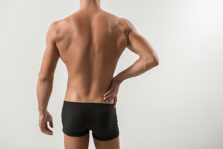 Treat backache. Close-up of back of young sportsman in black underwear. He is touching his loin while suffering from pain. Isolated background Stockfoto