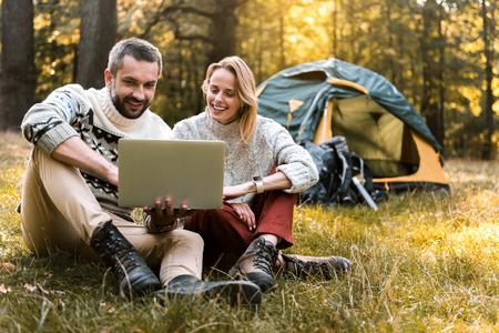 自然の中でポータブル コンピューターを使用して陽気な男女