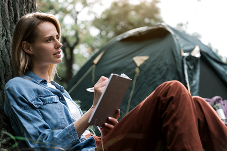 Inspired woman noting her thoughts during journey