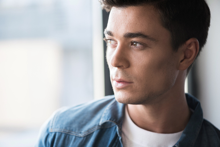 Pleasant stylish guy is thinking pensively