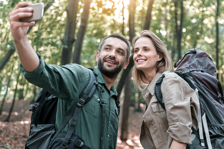 Happy man and woman photographing themselves on smartphone in nature