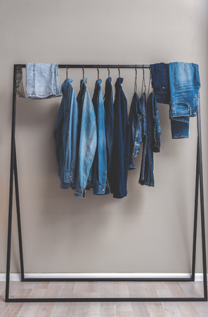 Various blue jean shirts and trousers are at hangers in wardrobe. Copy space. Nobody Stock Photo
