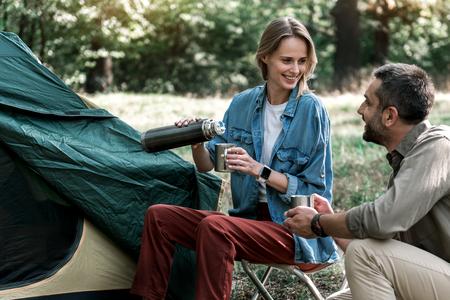 Joyful lovers drinking hot beverage in forest