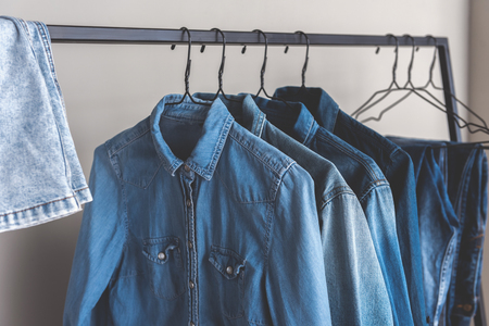 Different blue jean shirts are hanging on metal modern hangers. Nobody. Copy space on right side. Close up Stock Photo