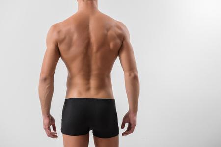Perfeição acetinada da pele. O close-up da parte traseira do desportista novo seguro está estando no roupa interior preto. Ele está mostrando seu corpo musculoso treinado. Isolado e copie o espaço no lado direito