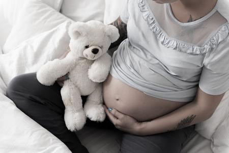 Zwanger meisje dat handen op buik zet