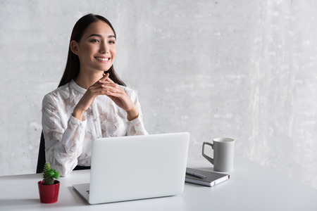 Dreamy smiling businesswoman sitting near desk