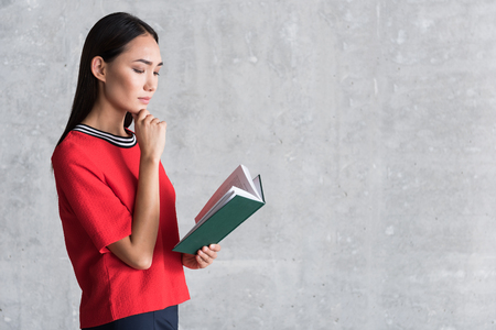 Attractive stylish girl is reading pensively