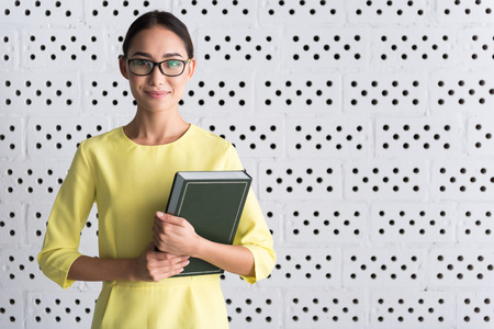 Charming young woman is posing with textbook