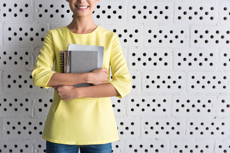 Cheerful elegant girl is posing with copybooks