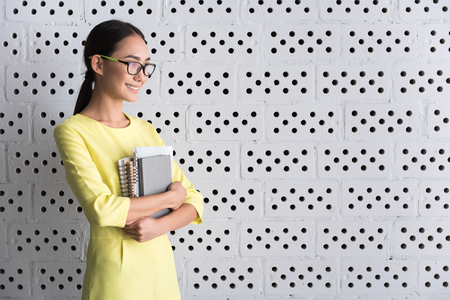 Positive young woman is holding notepads Stock Photo