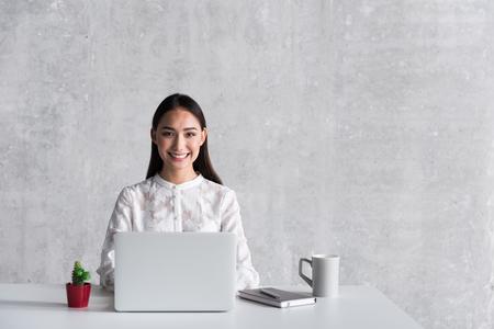 Mujer sonriente hilarante que localiza en oficina