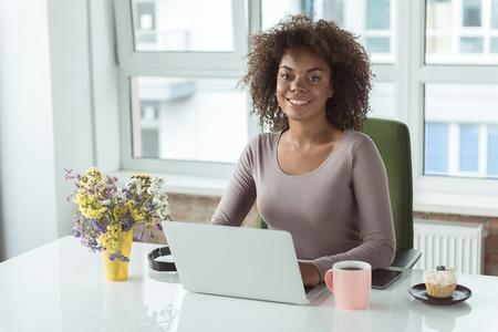 beaming: Beaming woman having job on laptop Stock Photo