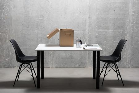 흰색 테이블 및 회색의 자에 서있는 검은 자. 노트북 컴퓨터, 연필 및 골 판지 상자가 그것에 있습니다. 가구 개념 스톡 콘텐츠 - 88168569