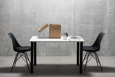 White table and black chair situating in gray room. Notebook computer, pencils and cardboard box are on it. Furniture concept 版權商用圖片
