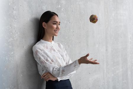Cheerful female upcasting rubber sphere Stok Fotoğraf