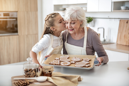 Happy child thanking grandma for sweet pastry Standard-Bild