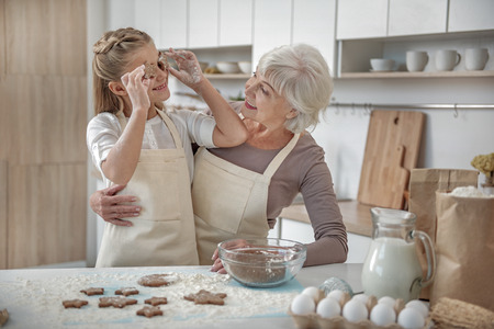 Carefree child enjoying baking process with her grandmother