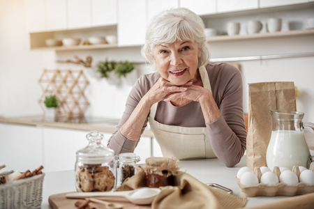 Cheerful old woman cooking at home