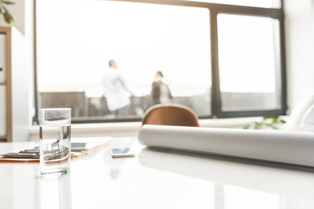 Close up of glass with water is on desk near other necessary things. People standing on balcony at background. Copy space on right side Stock Photo