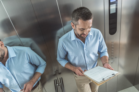 Confident professional guy is rising in lift Stock Photo - 88476744